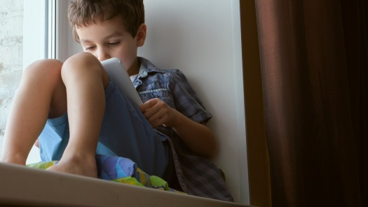 BOTTOM VIEW: Cute little boy uses a white tablet PC on a windowsill at home